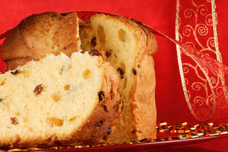 Panettone the italian Christmas fruit cake served on a red glass plate over a red background with red and golden ribbon. Selective focus.
