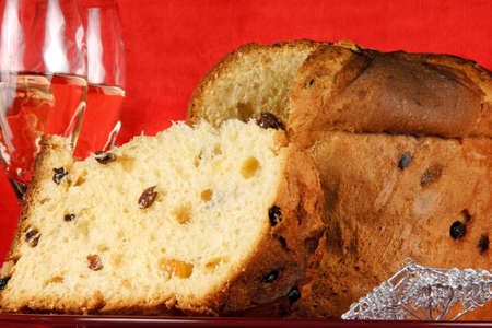 Panettone the italian Christmas fruit cake served on a red glass plate over a red background with silver star decorations and two glasses of champagne. Selective focus. Stock Photo