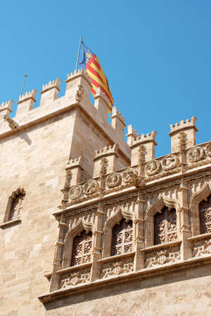 Detail of the Lonja de la Seda of Valencia in Spain and the valencian flag. This small complex of late gothic buildings, originally was used to trade silk.  photo