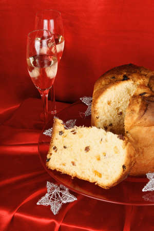 Panettone the italian Christmas fruit cake served on a red glass plate over a red background with silver star decorations and two glasses of sparkling wine (spumante). Selective focus. Stock Photo