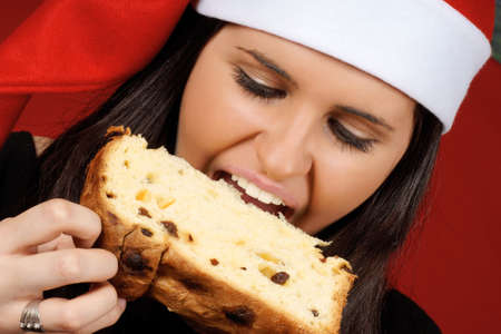 Beautiful 18 years old Santa Claus girl eating panettone, the italian Christmas fruit cake over a red background photo
