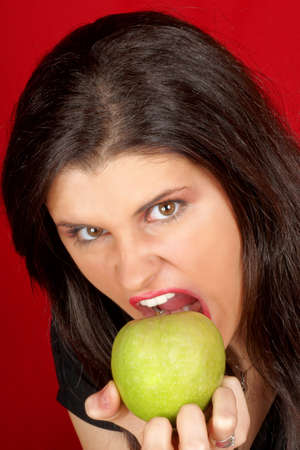 Angry beautiful young woman with green apple portrait over a red background. photo