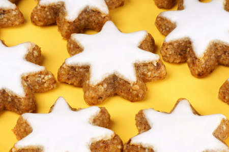 german swiss: Close-up of some cinnamon star cookies (in german Zimtsterne) are typical german and swiss Christmas cookies. Over a yellow background.