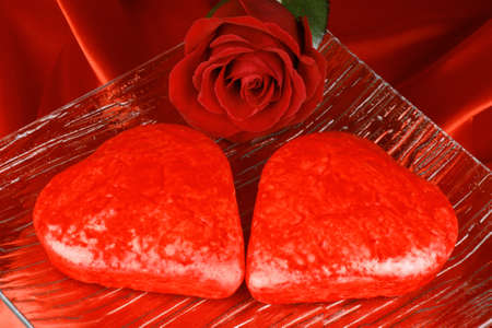 Two red heart shaped cakes and a rose over a red background for Valentine's Day