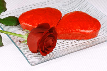 Two red heart shaped cakes and a rose for Valentine's Day