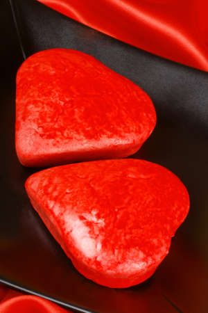 Two red heart shaped cakes on a black plate over a red background for Valentine's Day Stock Photo