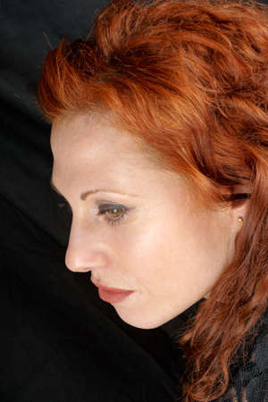 Side-face of a caucasian woman with red hair and brown eyes. Over a black background. photo