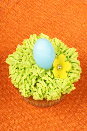 Fancy Easter cupcake decorated with sugar flower and hard sugar coated chocolate egg over an orange background. With copyspace. photo