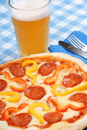 Set table with hot spicy pizza with salami and bell peppers and a glass of beer. Stock Photo - 9631743