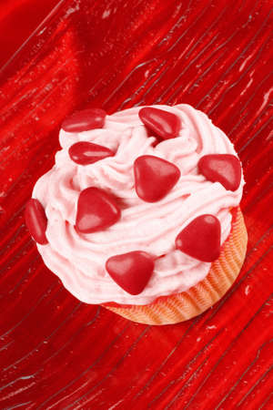 sugarcoated: Fancy Valentines Day cupcake decorated with small red sugar-coated chocolate hearts Stock Photo