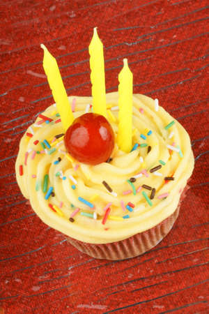 Birthday cupcake with lemon buttercream and three candles photo