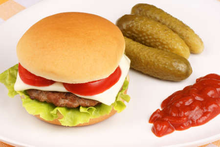 Mini cheese burger with tomato and lettuce and some pickles and ketchup on a white dish.