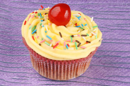 Fancy cupcake with lemon buttercream, sprinkles and candied cherry over a pink background. Selective focus. photo