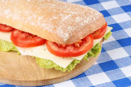 panino: Primer plano de un italiano panino (s�ndwich) de pan chapata reci�n horneado, lechuga, queso y tomate, DOF, enfoque selectivo. Foto de archivo