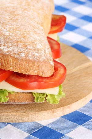 panino: Close-up of an italian panino (sandwich) with freshly baked ciabatta bread, lettuce, cheese and tomato, Shallow DOF, selective focus.