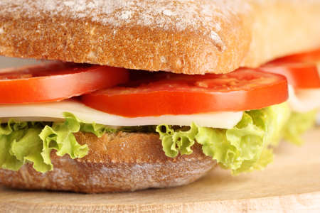 ciabatta: Close-up of an italian panino (sandwich) with freshly baked ciabatta bread, lettuce, cheese and tomato. Extreme shallow DOF, selective focus. Stock Photo