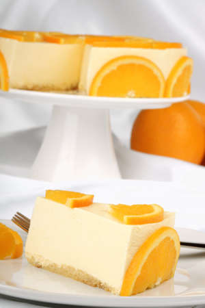 Orange bavarian cream slice (bavarese) with dessert fork on a white porcelain dish. Selective focus and shallow DOF