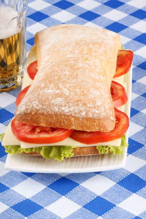 panino: Primer plano de un italiano panino (s�ndwich) de pan chapata reci�n horneado, lechuga, queso y tomate. En el fondo de un vaso de cerveza. Enfoque selectivo. Foto de archivo