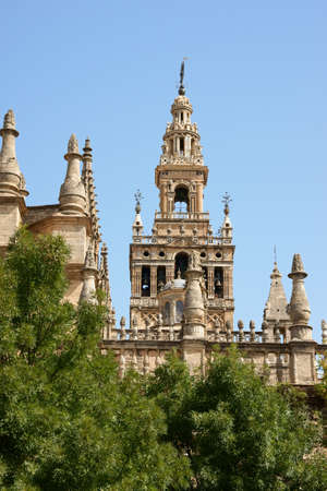Detail of the gothic and baroque Cathedral of Seville and the famous bell tower called La Giralda that was previously a minaret of the Berber Almohad period in Spain
