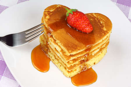 Heart-shaped pancakes with syrup and a strawberry on a white dish  A perfect breakfast for Valentine