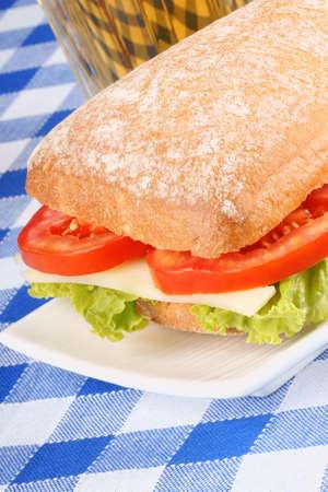 panino: Primer plano de un s�ndwich de panino italiano con pan ciabatta reci�n salido del horno, lechuga, queso y tomate en el fondo de un vaso de cerveza, enfoque selectivo