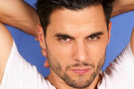 brown eyes: Apuesto hombre de 30 años con el pelo negro y los ojos marrones retrato sobre un fondo azul claro