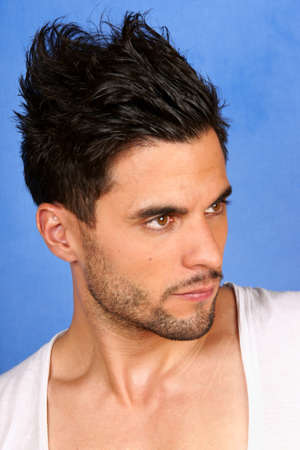 30 years old man: trendy 30 years old man with black hair and brown eyes portrait over a light blue background