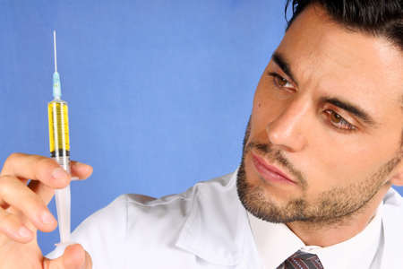 Mid adult doctor holding a syringe with yellow medicine  With copy space photo