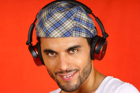 30 years old man: Smiling 30 years old man with beret and earphones over an orange background