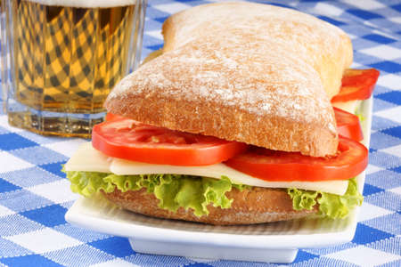 panino: Close-up of an italian panino (sandwich) with freshly baked ciabatta bread, lettuce, cheese and tomato. In the background a glass of beer. Selective focus. Stock Photo