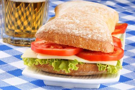 panino: Primer plano de un italiano panino (sandwich) con pan ciabatta reci�n salido del horno, lechuga, queso y tomate. En el fondo de un vaso de cerveza. Enfoque selectivo.