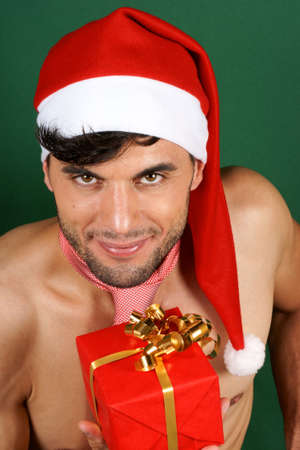 Sexy smiling Santa Claus holding a Christmas present over green background photo