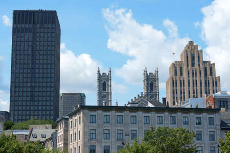 Montreal, Canada - July 26, 2008: glimpse of downtown Montreal with Aldred Building on the right, the towers of Notre Dame Cathedral in gothic revival style by architect James O'Donnel and some modern skyscrapers. Stock Photo - 18017531