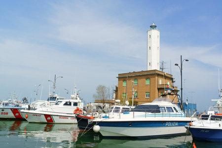 coast guard: Marina di Ravenna, Italy - April 13, 2013: coast guard and police boats in the port of Marina di Ravenna facing Adriatic Sea. In the background the lighthouse of the coast guard.