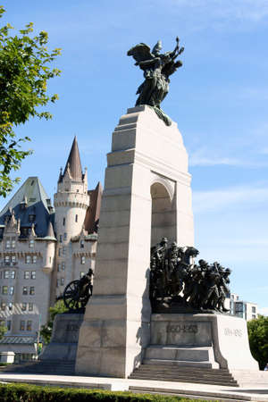 Ottawa, Canada - August 8, 2008: National War Memorial designed by Vernon March and unveiled by King George VI in 1939. The monument is composed of 23 bronze figures and a stone arch. In the background the castle like Chateau Laurier Hotel in downtown Ott