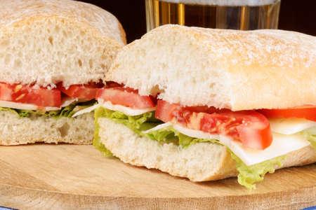 panino: Primer plano de un italiano panino (sandwich) con pan ciabatta reci?n salido del horno, lechuga, queso y tomate. En el fondo de un vaso de cerveza. Enfoque selectivo.