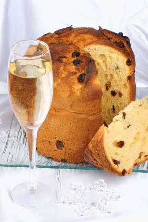 Panettone the italian Christmas fruit cake and a glass of spumante (champagne) over a white background. Selective focus.