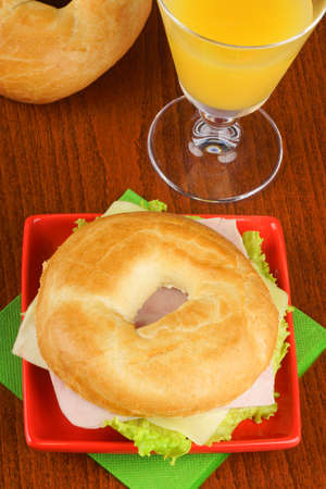 jewish cuisine: Bagel with ham, cheese and lettuce served on a red dish and a glass of orange juice over a wooden background