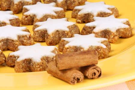 german swiss: Cinnamon star cookies  in german Zimtsterne , typical german and swiss Christmas cookies on a yellow plate  Stock Photo