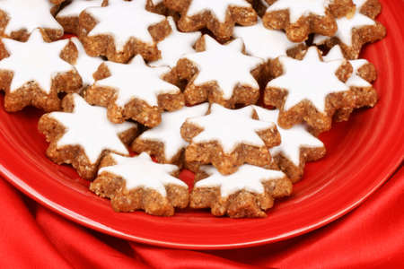 german swiss: Cinnamon star cookies  in german Zimtsterne , typical german and swiss Christmas cookies on a red plate over a red fabric background  Stock Photo