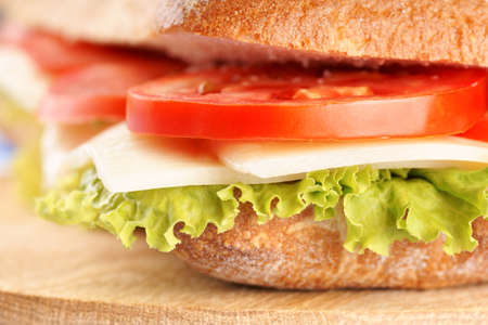 panino: Close-up of an italian panino (sandwich) with freshly baked ciabatta bread, lettuce, cheese and tomato. Extreme shallow DOF, selective focus. Stock Photo