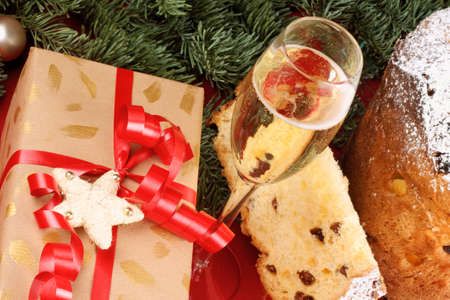 Christmas composition with a glass of italian spumante, panettone and a present in front of a Christmas tree Stock Photo - 23554487