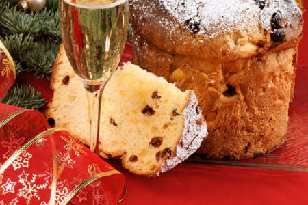 Christmas composition with a glass of italian spumante, panettone and a ribbon in front of a Christmas tree photo
