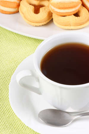 Close-up of a cup of tea and some shortcrust pastry biscuits over a light green  photo