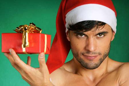 Sexy souriant Santa Claus, tenant un cadeau de Noël sur le mur vert