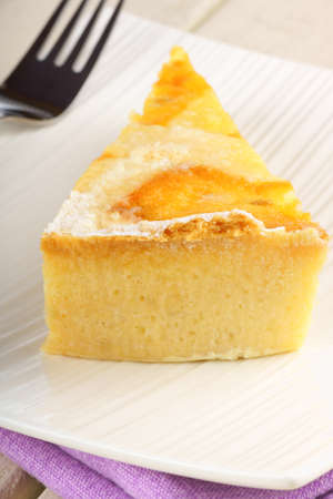 A slice of the original Easter cake from Naples called Pastiera, served on a white porcelain dish over a wooden background. This neapolitan traditional tart is made of shortcrust pastry filled with boiled wheat, ricotta cheese, candied fruit and orange bl photo