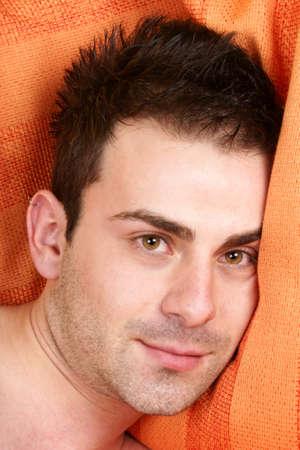 ojos marrones: Retrato de un joven so�ador con los ojos marrones y cabello casta�o sobre una almohada de color naranja. Foto de archivo
