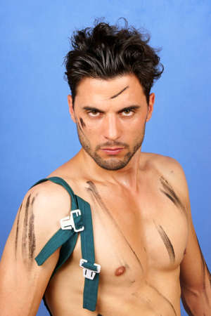 30 year old: Sexy shirtless greasy 30 year old caucasian worker looking at camera over a blue background.