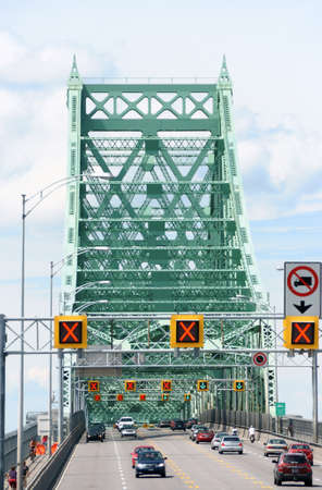 wa: Montreal, Canada - August 9, 2008: traffic on Jacques Cartier bridge crossing Saint Lawrence river in Montreal on a cloudy day. This truss cantilever bridge was built between 1925 and 1930 and took the name of Montreal Harbour Bridge until 1934 when it wa Editorial