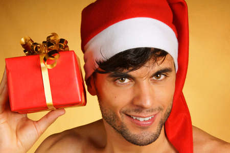 sexy santa claus: Sexy smiling Santa Claus holding a Christmas presents over yellow background